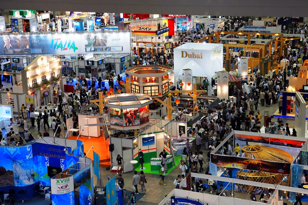 A large convention hall with many different booths and a large crowd