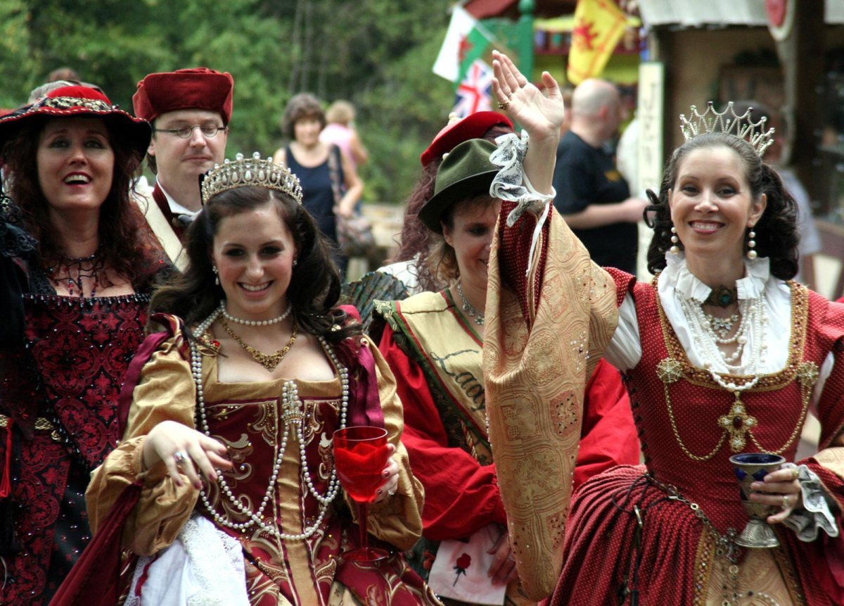 A group of women dressed in renaissance era clothing, with one being the queen.