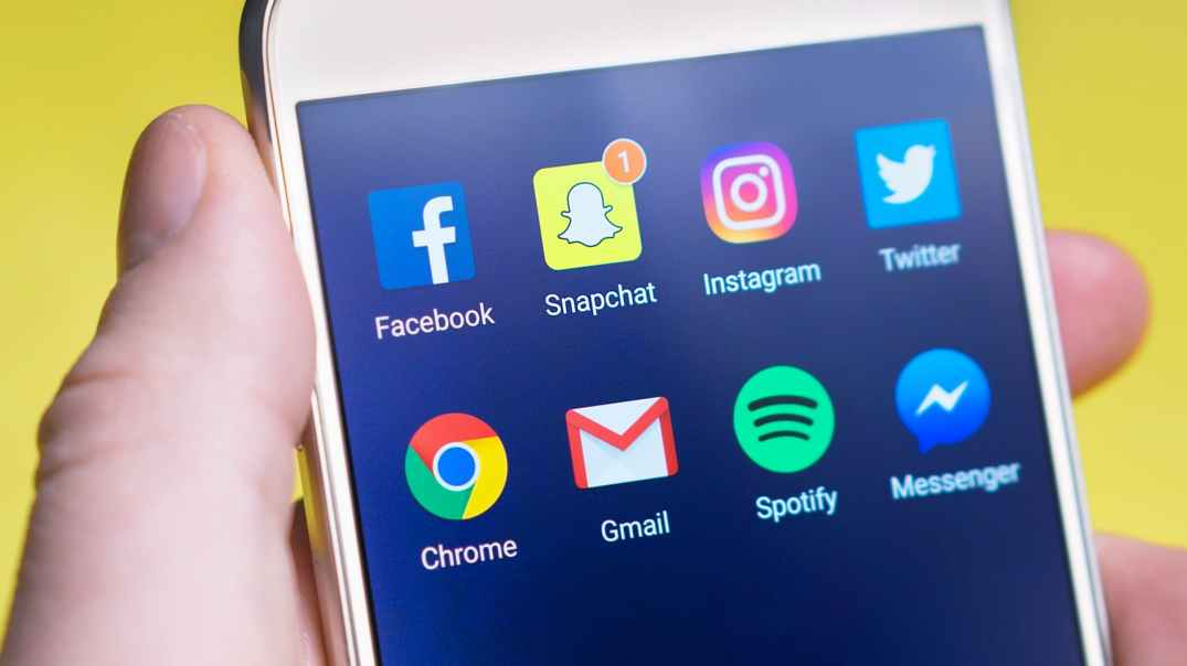An image of a person holding a phone with 8 social media icons on the screen. Facebook, Snapchat, Instagram, Twitter, Chrome, Gmail, Spotify, and Messenger.
